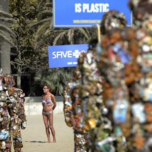 Coronita patrocina una exposición medioambiental que ha colocado 'hombres-basura' en plena playa de Barcelona