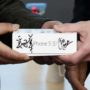 Tim Cook firma iPhones en un evento para celebrar su acuerdo con China Mobile