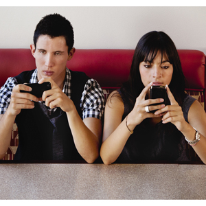 Twenty year-old couple sitting in a cafe banquette