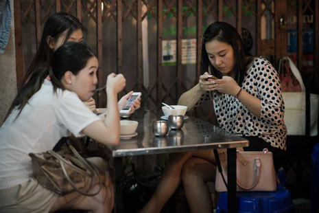 This picture taken on March 19, 2013 shows women looking at their smartphones while having dinner at a street food restaurant in Bangkok. A recent Facebook-sponsored study showed smartphone owners are often connected all day. People can be found glued to their smartphones at airports, on trains, in restaurants and even while walking on the street, creating a disconnection from their immediate surroundings. Smartphone sales are expected to continue to surge in 2013 with some 918 million units to be bought worldwide. AFP PHOTO/ Nicolas ASFOURI        (Photo credit should read NICOLAS ASFOURI/AFP/Getty Images)