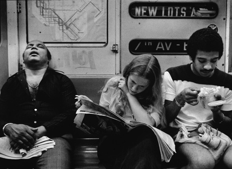 A view of three people sitting on the Number 2 line (7 Avenue Express) IRT subway, New York, 1970s. One man sleeps, a young woman reads a newspaper, and a young man eats. (Photo by Tony Vaccaro/Getty Images)