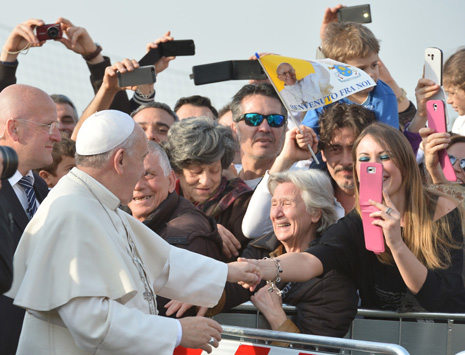 "People take pictures with their mobile phones as Pope Francis arrives to visit the Roman parish of ""Santa Maria dell'Orazione"" in Guidonia Montecelio near Rome on March 16, 2014.  AFP PHOTO / ALBERTO PIZZOLI        (Photo credit should read ALBERTO PIZZOLI/AFP/Getty Images)"