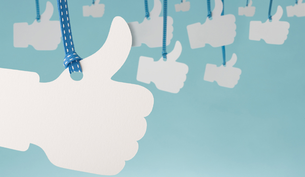 White thumbs up hanging from blue ribbon