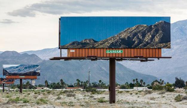 Unos carteles de publicidad muestran el paisaje que hay justo detrás de ellos