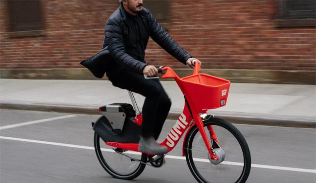 Uber se sube a la bici acomodándose en el sillín de la empresa Jump