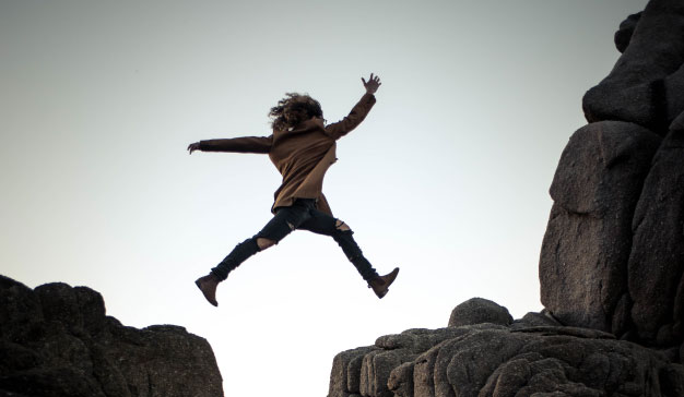 imagen de una mujer saltando entre las rocas