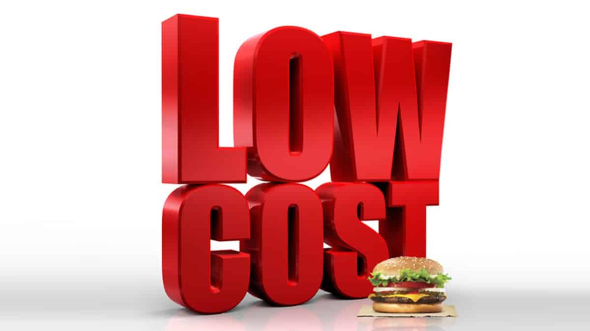 """Palabra """"Low Cost"""" en letras rojas detrás de una Whopper con queso"""